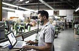 Technician using laptop while working in a factory