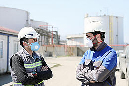 Workers are talking with protective masks for coronavirus (covid-19) epidemic in the construction field. In humans, coronaviruses cause respiratory tract infections that can range from mild to lethal.